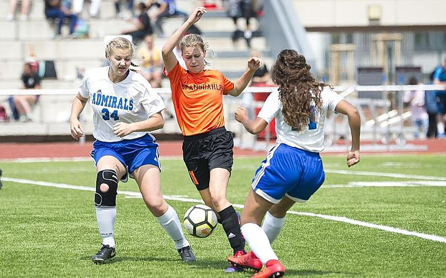 Spangdhalem's Ava Bohn dribbles between Rota's Jacqueline Holtz, left, and Erika Lathem during the DODEA-Europe Division II soccer championship in Kaiserslautern, Germany, on Thursday, May 24, 2018. Spangdhalem won the game 2-0.