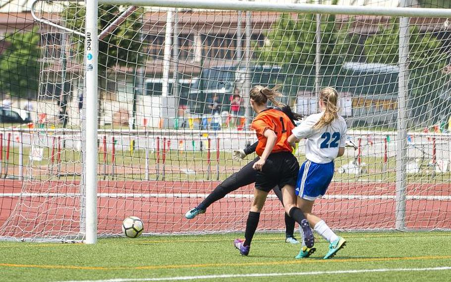 Spangdhalem's Ava Bohn gets a goal past both Rota's goalkeeper Arielle Reese and Samantha Miller, right, during the DODEA-Europe Division II soccer championship in Kaiserslautern, Germany, on Thursday, May 24, 2018.
