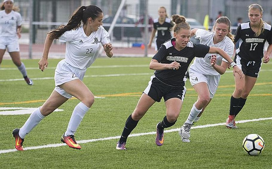 Stuttgart's Adan Maher cuts between Ramstein's Rocio Fernandez, left, and Brittany Cunningham during the DODEA-Europe Division I soccer championship in Kaiserslautern, Germany, on Thursday, May 24, 2018. Stuttgart won the game 6-5 after a shootout.
