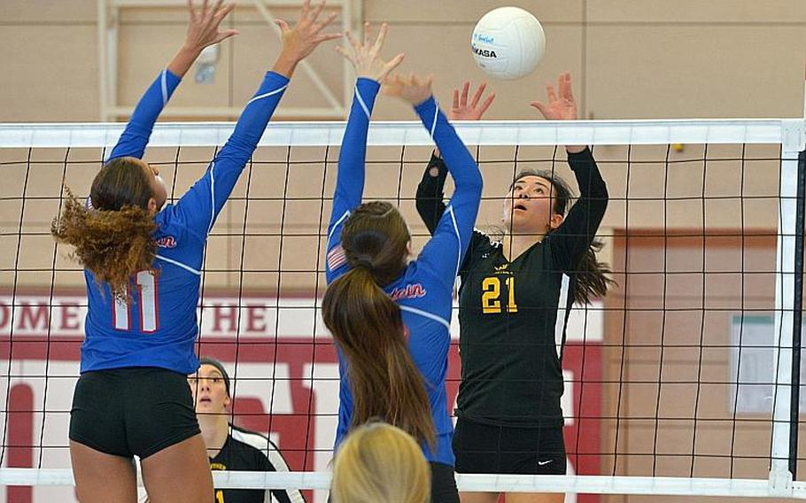 Stuttgart's Karen Kosinski lobs the ball over the Ramstein defense of Masaya Archbold, left, and Ahmarie Young in the Division I final at the DODEA-Europe volleyball championships in Kaiserslautern, Germany. Stuttgart took the title with a 25-23, 25-18, 25-10 win over Ramstein.