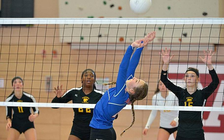 Ramstein's Sydney Gabriel sets the ball for a teammate as Stuttgart's Skye DaSilva Mathis, left, and Geneva Barriger wait to defend across the net. in the Division I final at the DODEA-Europe volleyball championships in Kaiserslautern, Germany. Stuttgart took the title with a 25-23, 25-18, 25-10 win over the Royals.