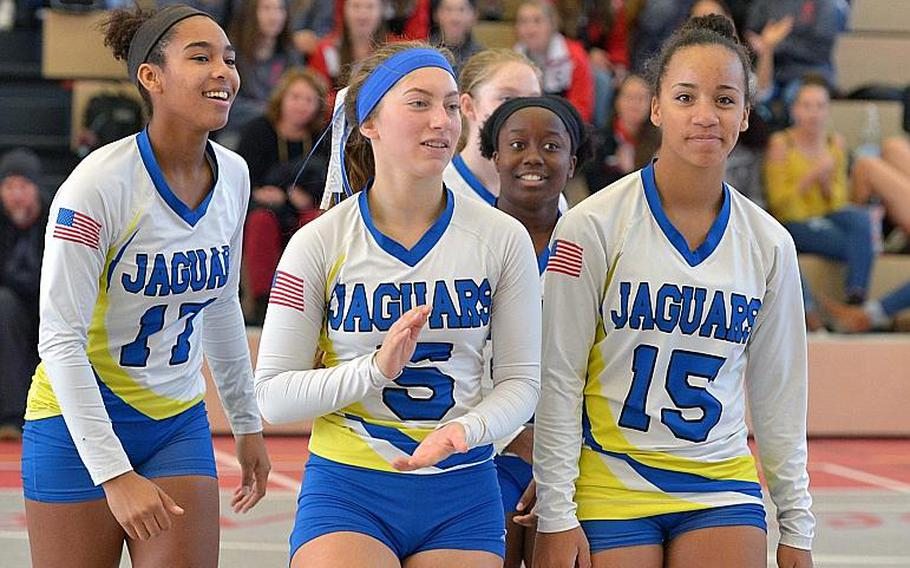 Sigonella's D'Anna Holland, Jessica Jacobs, Eliza Moore and Averi Chandler, from left, smile and clap as they walk off the court after defeating Brussels 25-14, 25-13, 23-25, 25-17 in the Division III title game at the DODEA-Euope volleyball championships in Kaiserslautern, Germany.