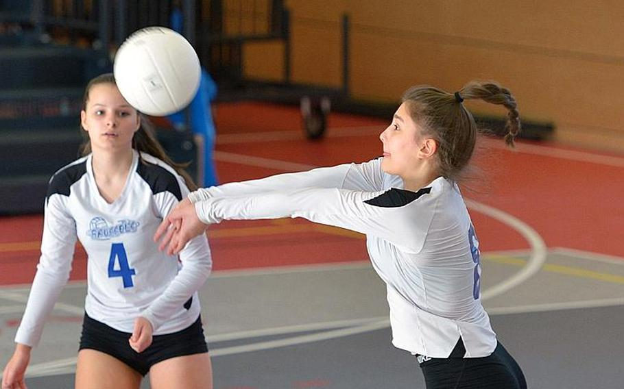 Nina Duvnjak of Brussels hits the ball as teammate Olivia Friedhoff watches in the Division III final of the DODEA-Europe volleyball championships in Kaiserslautern, Germany, Saturday, Nov. 3, 2018. Sigonella took the title with a 25-14, 25-13, 23-25, 25-17