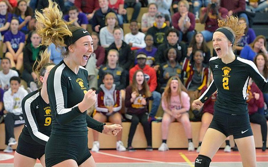 Carly Sharp, left, and Rachel Sanborn celebrate the Panthers' 25-23, 25-18, 25-10 win over Ramstein in the Division I final at the DODEA-Europe volleyball championships in Kaiserslautern, Germany, Saturday, Nov. 5, 2018. Coming to join the celebration covered at far left is Audrey Moeding.