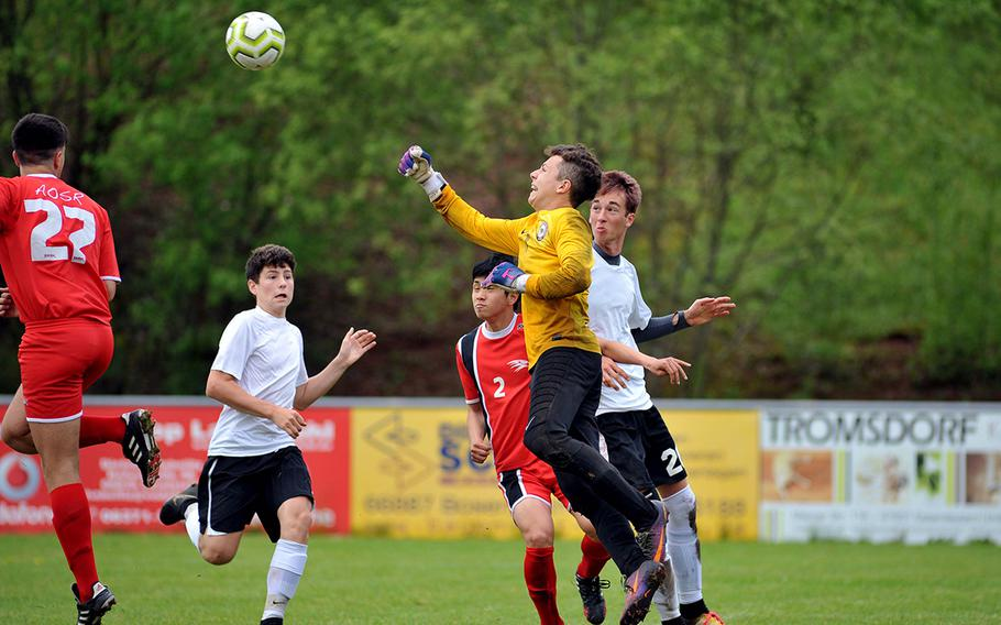 AOSR keeper Martin Jijena goes for the ball against AFNORTH's Preston Guza and Lisse Bohlen, right, as teammates Giuseppe Amara, left, and Seung Hyun Na watch the action in a Division II semifinal in Reichenbach, Wednesday, May 22, 2019. AOSR won the game 1-0 to advance to Thursday's final against Aviano.