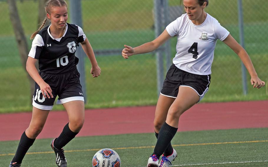 Zama's Aubrey Giles and Daegu's Jasmine Litton try to play the ball during Wednesday's Far East Girls Division II soccer tournament pool-play match. The Trojans won 7-0.