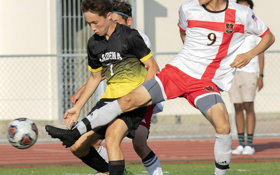 Kadena's Logan Taylor and Kinnick's Kai Sullivan battle for the ball during Wednesday's Far East Boys Division I Soccer Tournament round-robin. The Red Devils won 3-2.