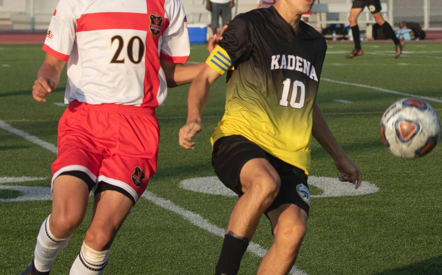 Kadena's Kian Smith and Kinnick's Daniel Burke chase the ball during Wednesday's Far East Boys Division I Soccer Tournament round-robin. The Red Devils won 3-2.