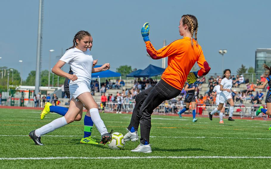 Spangdahlem's Chesney Tieyah drives to the goal as Hohenfels' goalie Kaetlyn Traux comes out to meet her during the girls Division III DODEA-Europe soccer championship game, Thursday, May 23, 2019. Spangdahlem won the game 4-2.