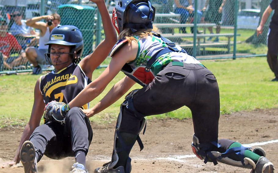Kubasaki catcher Jocelyn Powell tries to tag American School In Japan baserunner Erin Dowich during Thursday's round robin game in the Far East Division I softball Tournament. The Mustangs won 11-10.