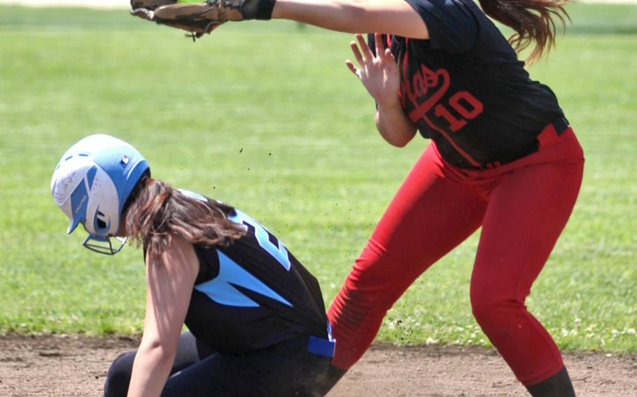 Osan's Satomi Swayne slides in safely under the throw to E.J. King's Yumika Randall during Thursday's round-robin game in the Far East Division II softball tournament. The Cougars won 10-4.