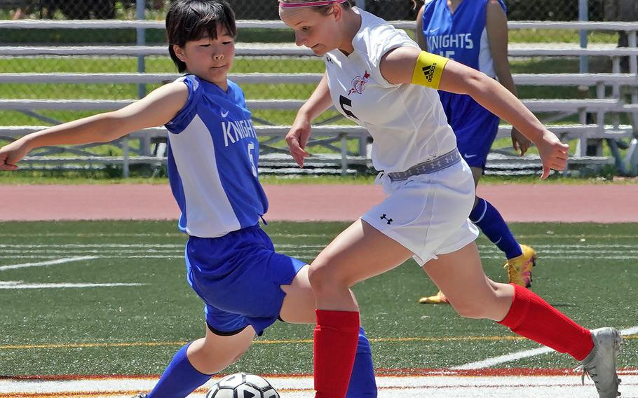 Christian Academy Japan's Miyuki Yamakawa and E.J. King's Gabi Shultz try to play the ball during Thursday's round-robin in the Far East Division II girls soccer tournament. The teams battled to a 1-1 draw.