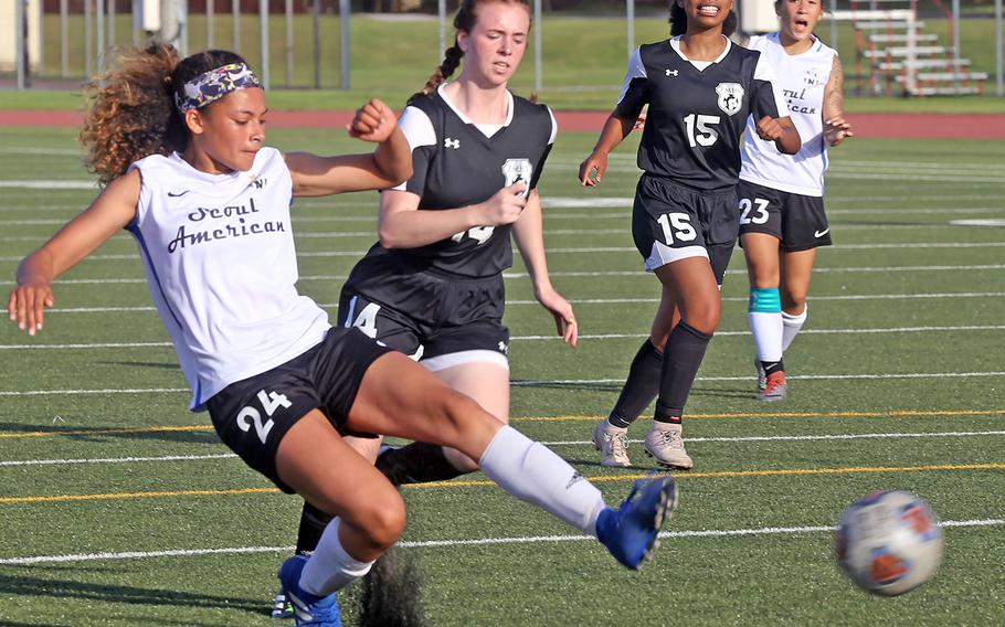 Seoul American's Mya Rolison boots the ball past Zama's Abigail Logan during Thursday's round robin in the Far East Division II girls soccer tournament. The Trojans won 5-2.