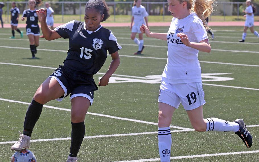 Zama's Midori Robinson and Osan's Davinia Wengert battle for the ball during Thursday's round robin in the Far East Division II girls soccer tournament. The Trojans won 7-0.