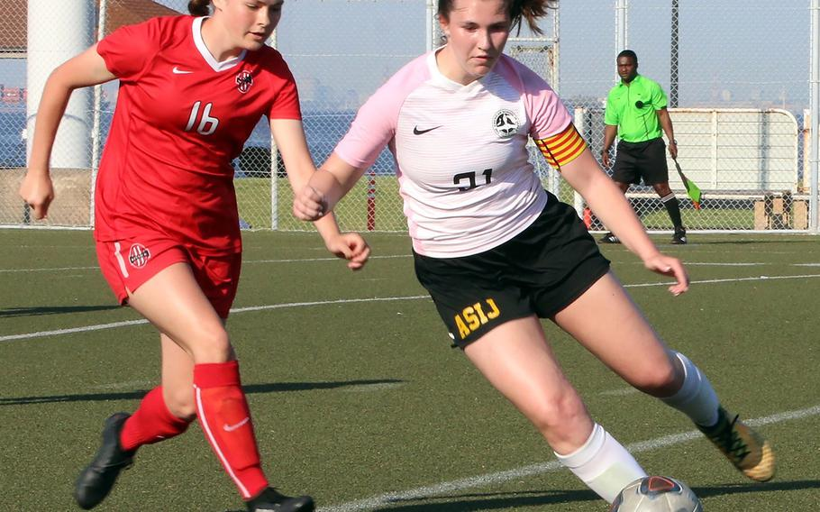 ASIJ's Ava Vander Louw plays the ball as Kinnick's Lindsey Boran defends during Thursday's semifinal in the Far East Division I girls soccer tournament. The Red Devils won 3-1 on penalties.