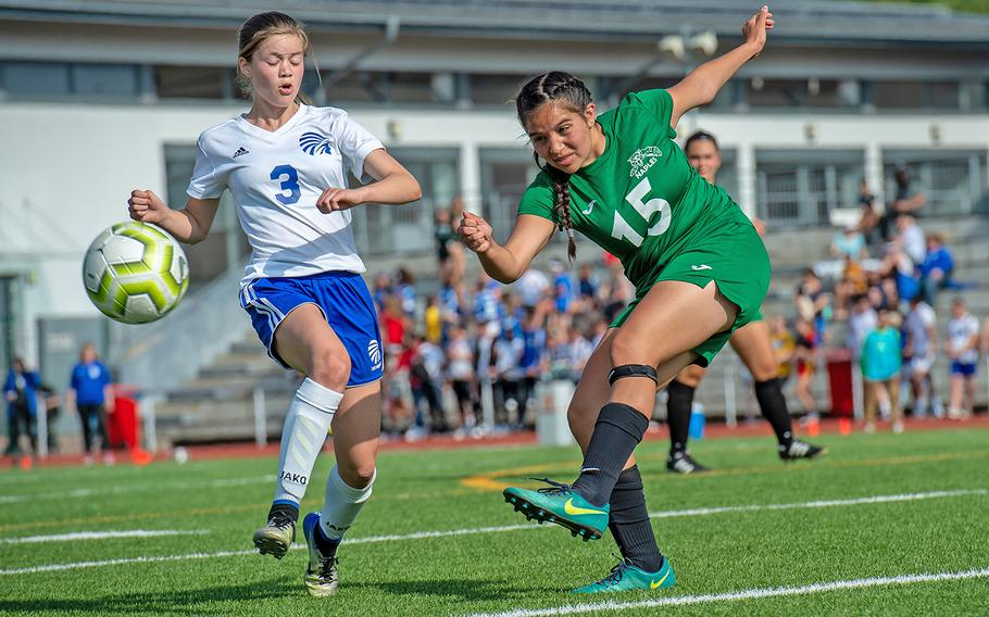 Naples' Thalia Galindo takes a shot as Wiesbaden's Greta Lambert tries to block during the girls Division I DODEA-Europe soccer championship game, Thursday, May 23, 2019. Wiesbaden won the game 2-0.