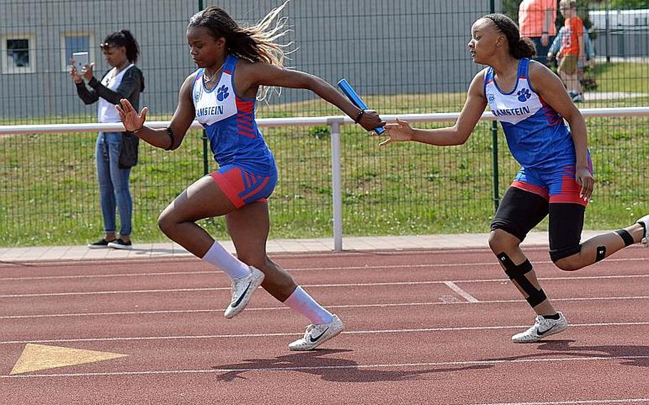 Ramstein's Aryal Allen takes the baton from Jarai Jones on their way to winning the 4x100-meter relay at the DODEA-Europe track and field finals in Kaiserslautern, Saturday, May 25, 2019. Along with teammates Shannon McCray and Casey McCollum they won the race in 50.87 seconds.