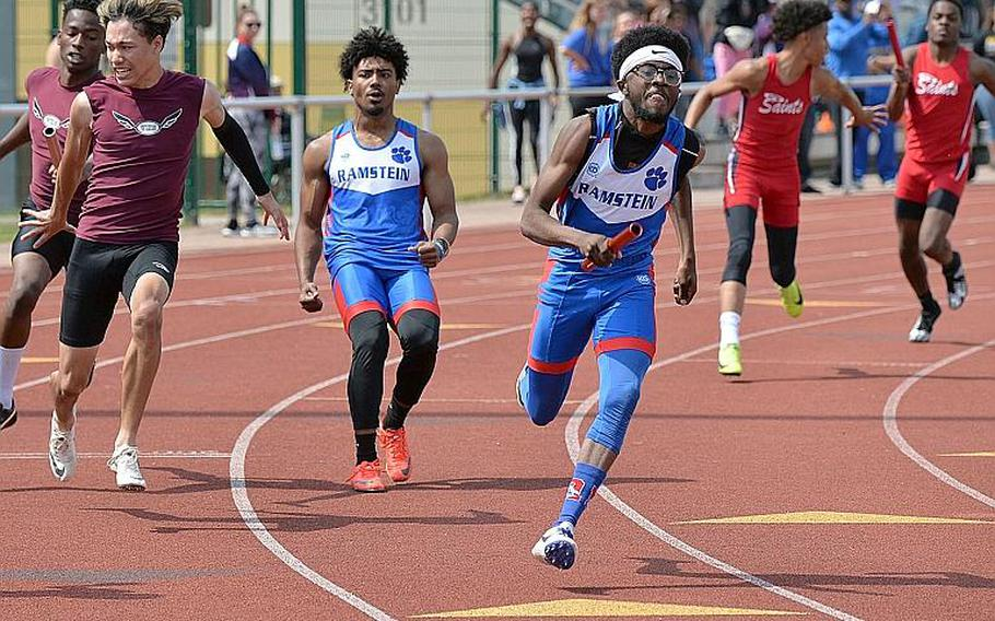 Ramstein's Cameron Chester sprints off after taking the baton from Dominique Arizpe in the boys 4x100-meter relay at the DODEA-Europe track and field finals in Kaiserslautern, Saturday, May 25, 2019. Along with teammates Isaiah Allen and Jason Jones Jr. they took the title in 43.71 seconds.