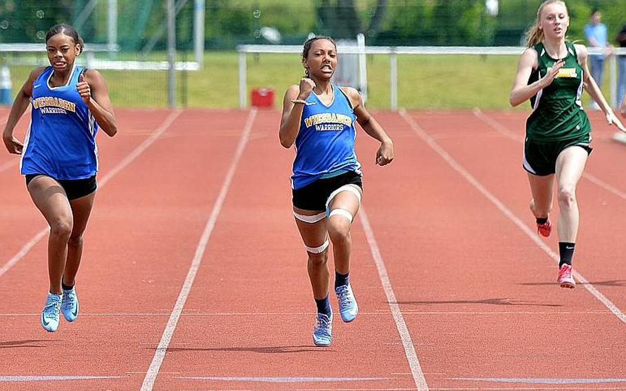Wiesbaden's Whitney Bivins sprints to the finish to capture the 200-meter dash ahead of teammate Ashanti Scott , left, in 26.20 seconds at the DODEA-Europe track and field finals in Kaiserslautern, Saturday, May 25, 2019. At right is Alconbury's Marissa Kastler, who finished fourth.