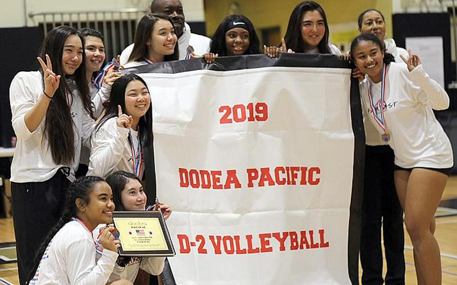 Zama players and coaches gather round the Far East Division II banner.