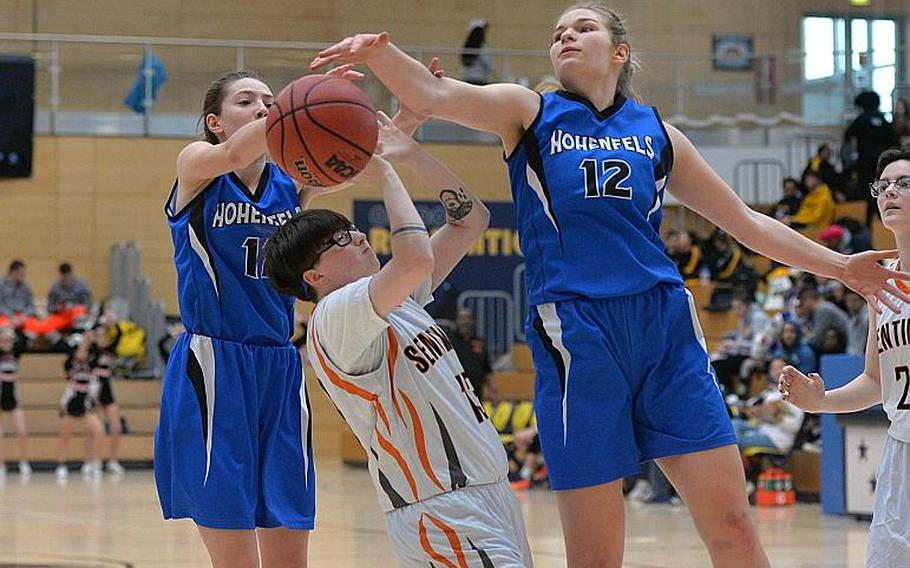 Destiny Tyler of Spangdahlem gets caught between Allison Wenger, left, and Tiana Rodgers as the battle for a rebound in the girls Division III final at the DODEA-Europe basketball championships in Wiesbaden, Germany, Saturday, Feb. 22, 2020. Spangdahlem won 37-21.