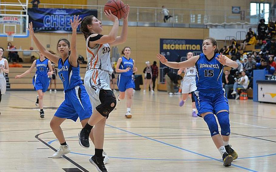 Bridget Donovan of Spangdahlem takes a shot as June Smith of Hohenfels comes in to defend in the girls Division III final at the DODEA-Europe basketball championships in Wiesbaden, Germany, Saturday, Feb. 22, 2020. At left is Kate Farrell. Spangdahlem won 37-21.