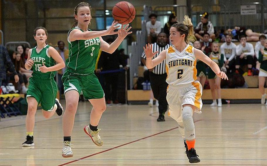 Gabi Schultz of SHAPE passes to a teammate as she takes the ball up the court, guarded by Olivia Sullens of Stuttgart in the girls Division I final at the DODEA-Europe basketball championships in Wiesbaden, Germany, Saturday, Feb. 22, 2020.