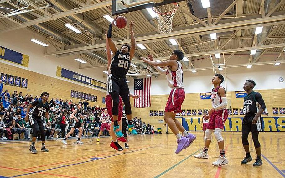 Naples' Tyrell Holland grabs a rebound during the DODEA-Europe 2020 Division II Boys Basketball Championship game against Aviano at Wiesbaden High School, Germany, Saturday, Feb. 22, 2020. Naples won the game 40-35.
