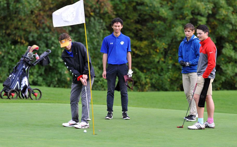 Ramstein's Matt Miller putts on the day's final hole at the DODEA-Europe high school golf championships in Wiesbaden, Germany, in October 2019, as teammate Chris Angeles, Stuttgart's Jonathan Keathley and Kaiserslautern's Mathias Perrin watch. Golfers will take to the links this season with coronavirus precautions.