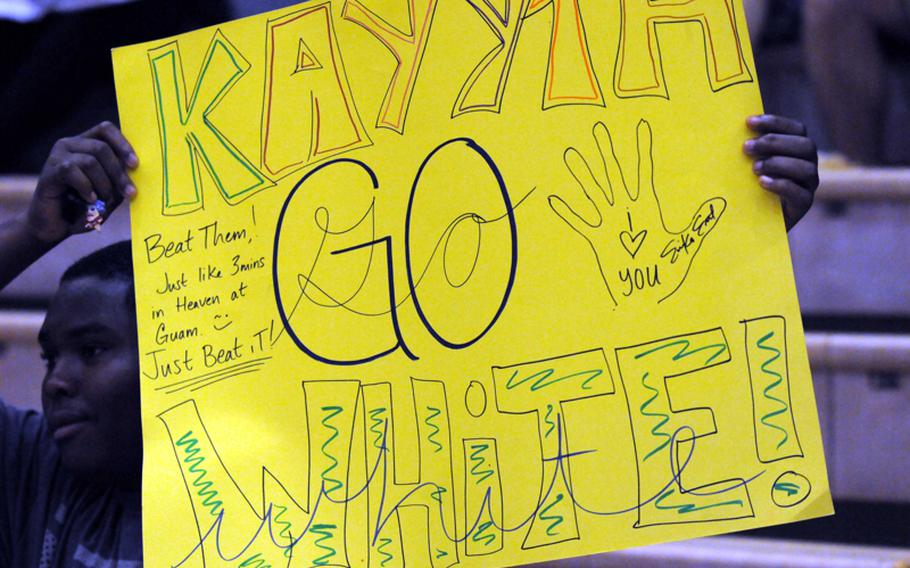 Yokota High School junior Phillip Burnett holds up a sign in support of Panthers senior setter Kathryn White during Tuesday's Kanto Plain Association of Secondary Schools girls volleyball match at Yokota Air Base, Japan. American School In Japan's Mustangs rallied from a one-set deficit to win 19-25, 25-20, 25-20, 25-10.