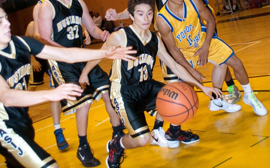 Liam Fukushima (21), Henry Wallrapp (32) and Drogan James (13) of American School In Japan Mustangs and Yokota Panthers' Morgan Breazell chase down a loose ball during the championship games Dec.. 18, 2011, in the American School In Japan Holiday Classic boys basketball tournament