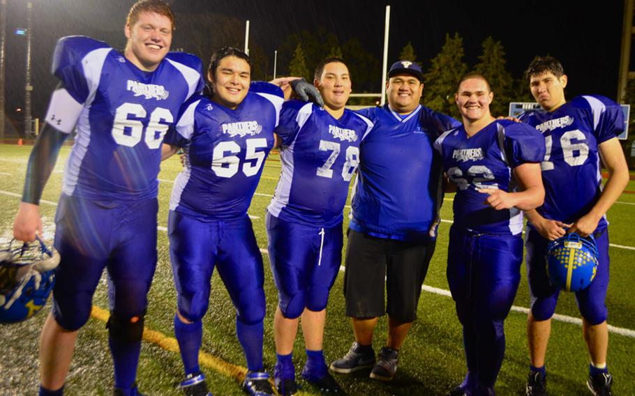From left, Yokota Panthers right tackle Jesse Hogan, right guard Dylan Kessler, center Victor Madaris, line coach Ernie Carrasco, left guard Jake Jackson and left tackle Max Lester, all of whom have been together since they were freshmen, celebrate the Panthers' second straight Far East Division I football title after Saturday's 55-8 romp over Kubasaki.