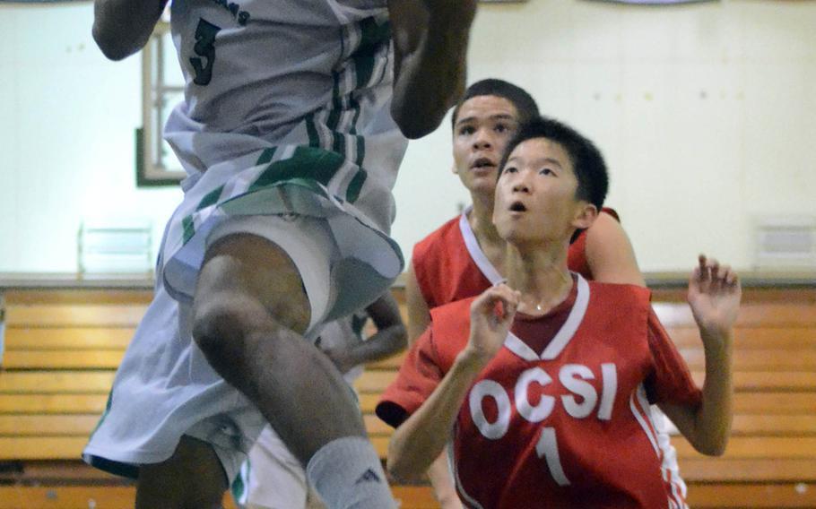 Kubasaki's DeQuan Alderman floats toward the basket past Okinawa Christian International defenders during Tuesday's Okinawa Activities Council boys high school season opener at Camp Foster, Okinawa. Kubasaki won 78-46.