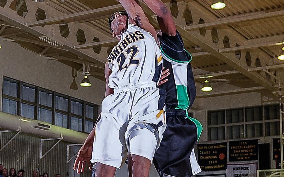 Kadena's Jamario Harris' shot is defended by Kubasaki's DeQuan Alderman during Friday's Okinawa Athletics and Activities Council boys high school basketball game at Kadena Air Base, Okinawa. The Dragons won 61-58.