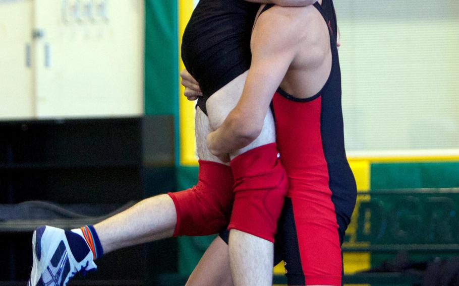 Nile C. Kinnick's' Brady Yoder lifts to throw E.J. King's David Jackson during Saturday's DODDS Japan dual-meet tournament at Misawa Air Base, Japan. Yoder won all but one of his bouts at 129 pounds and Kinnick won all five of its duals.
