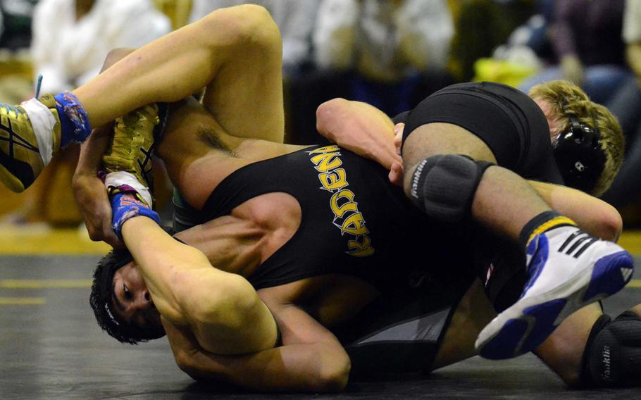 Kubasaki's Austin Cyr, back, tries to tilt Kadena's Elijah Takushi at 148 pounds during Wednesday's Okinawa Athletics and Activities Council high school wrestling dual meet at Kadena Air Base, Okinawa. Cyr rallied from an early 6-0 deficit to win a 17-16 decision.