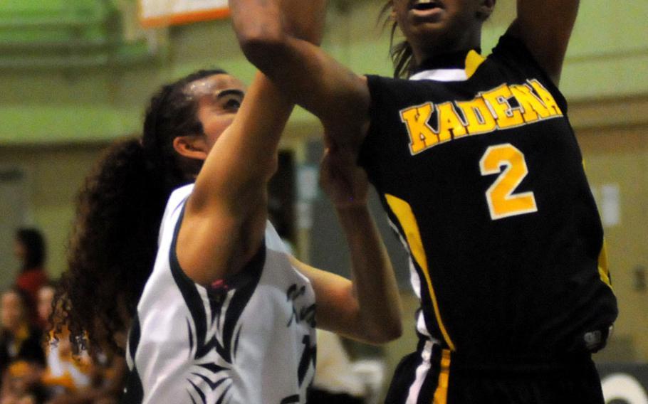 Kadena's Jasmine Rhodes shoots past Kubasaki's Ameyna Saunders-Jackson during Friday's Okinawa Athletics and Activities Council high school girls basketball game at Camp Foster, Okinawa. Kubasaki won 48-42, its first OAAC regular-season win over Kadena in 10 years.