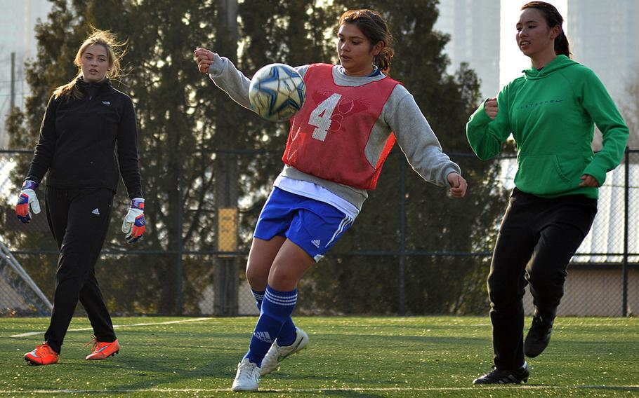 Seoul American defender Kayla Granado fields the ball between teammates Charley Smith and Lizzy Puskas during Wednesday's practice.