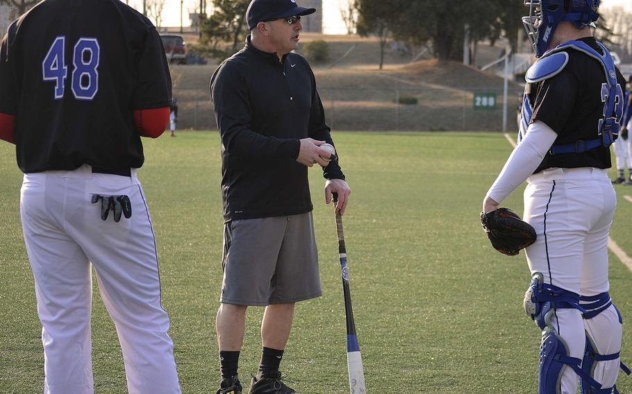 Seoul American coach Dean Florio talks things over with Falcons designated hitter Kent Hinchcliff and catcher Wayne White during Wednesday's practice.