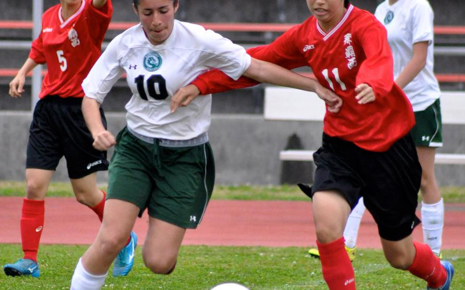 Kubasaki striker Marissa Mesquta and a Naha Nishi midfielder battle for the ball during Saturday's season-opening match for the reigning Far East Division I Tournament champion Dragons; they won 2-0.