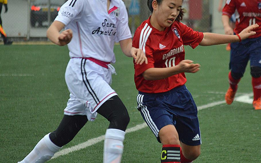 Seoul American's Hannah Frederick and Yongsan's Juhee Kim battle for the ball during Wednesday's Korea girls soccer match, which ended in a 1-1 draw.