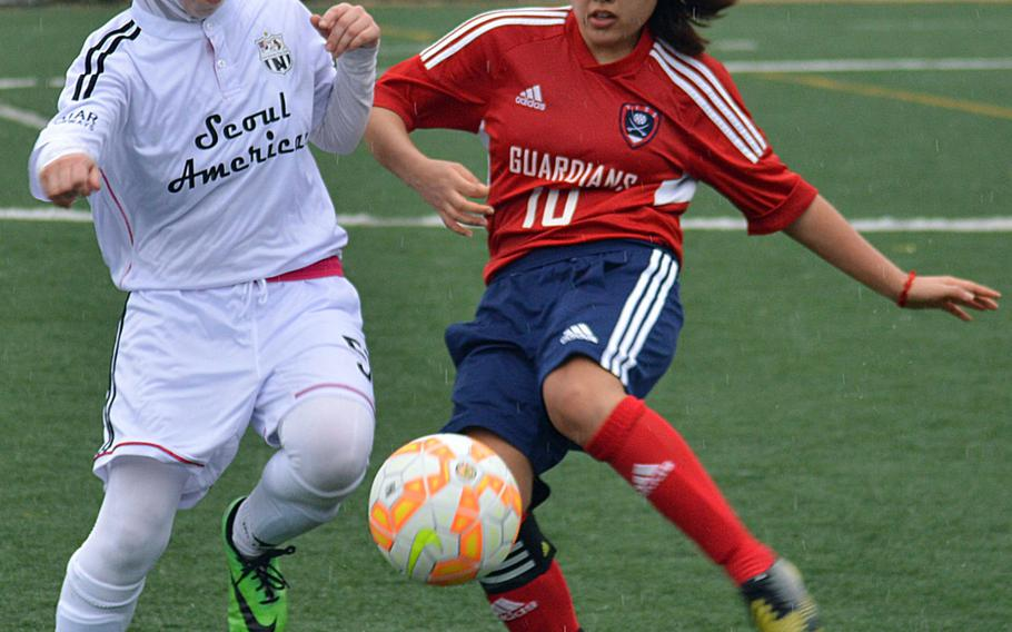 Seoul American's Mariam Sarver and Yongsan's Juhee Kim battle for the ball during Wednesday's Korea girls soccer match, which ended in a 1-1 draw.