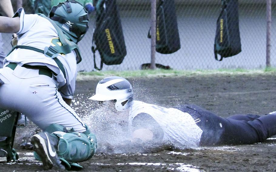 Zama's Jaron Brown gets a face full of lime and dust as he slides into the tag of Robert D. Edgren's Jackson Edmonds during Friday's DODDS Japan baseball game. The Trojans swept a twin bill from the Eagles 6-1 and 19-4.