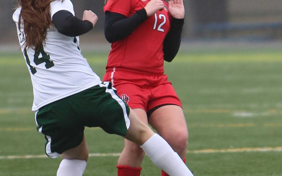 Robert D. Edgren's Josette Dooley and Nile C. Kinnick's Haley Mitchell scrum for the ball during Friday's DODDS Japan girls soccer match. The Red Devils won 8-0.