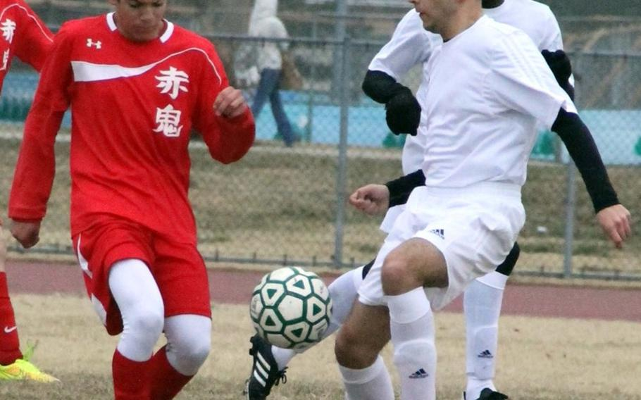Nile C. Kinnick's Chon Dareing and Robert D. Edgren's Gabriel Schultz battle for the ball during Friday's DODDS Japan boys soccer match. The Red Devils won 3-2.