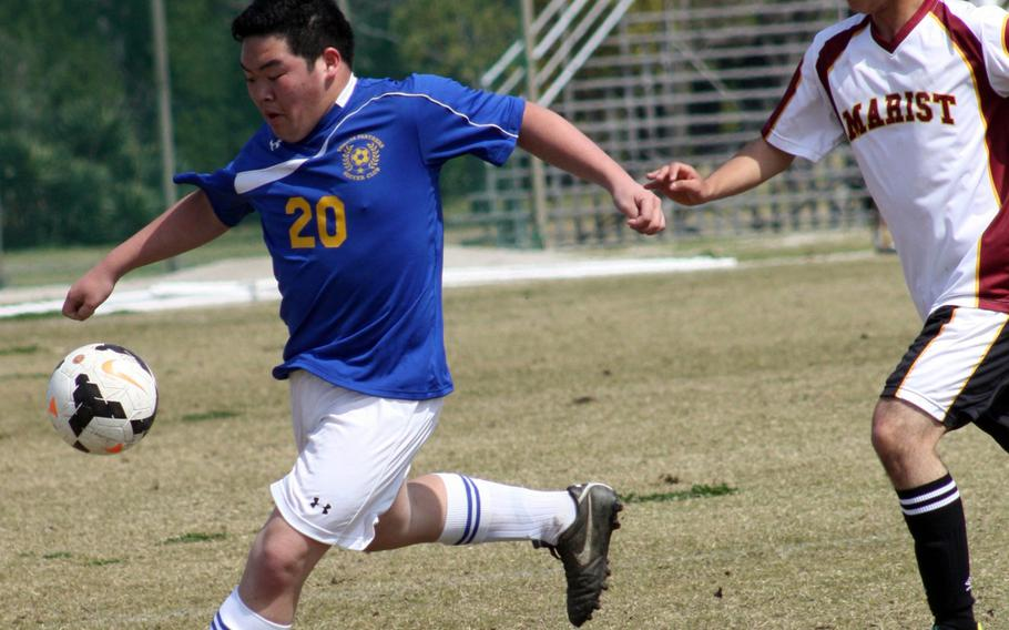 Yokota's Justin Pho boots the ball in front of Marist Brothers' Lucas Sant'Anna during Saturday's Perry Cup tournament match. The Bulldogs blanked the Panthers 1-0.