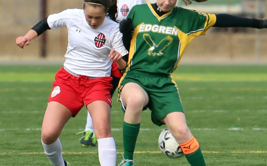 Nile C. Kinnick's Charla Johnson and Robert D. Edgren's Madeline Mattingly battle for the ball during Saturday's DODDS Japan girls soccer match. The Red Devils won 5-0 to sweep the weekend series.