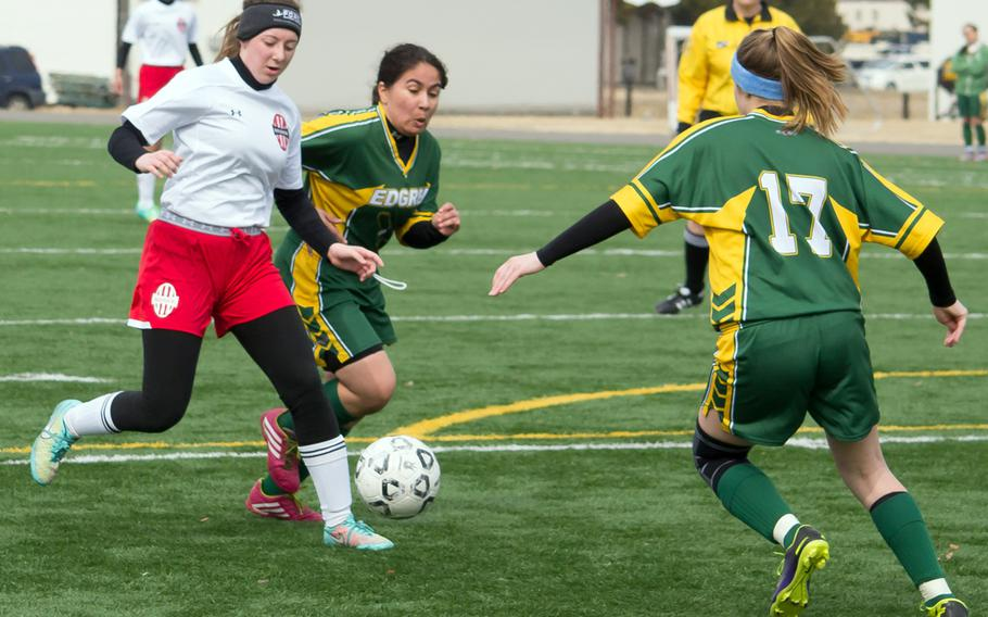 Nile C. Kinnick's Alyssa Leal and Robert D. Edgren's Jaymee Ronquillo and Emma Mattingly scrum for the ball during Saturday's DODDS Japan girls soccer match. The Red Devils won 5-0 to sweep the weekend series.