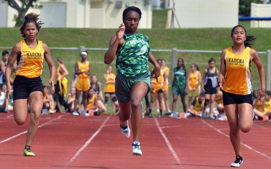 Kubasaki's Kaelyn Francis pounds for the finish, flanked by Kadena's Monet Baker and Apryl-Len Cabase during the girls 100-meter dash in Saturday's Okinawa season-opening track and field meet. Francis clocked 12.02 seconds on the stopwatch, the second-fastest time in Pacific history by any timing method.