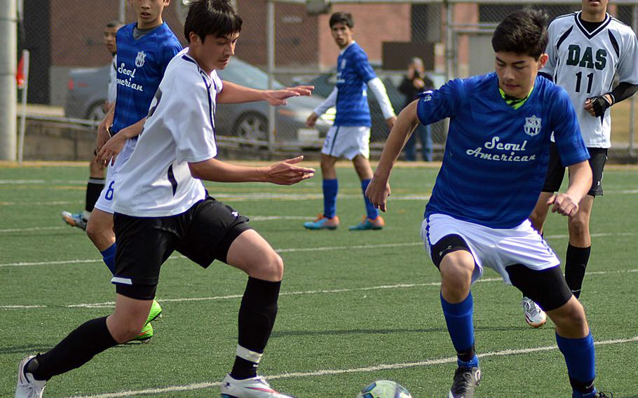 Daegu's Jonas Langlois and Seoul American's Nick Gagnet battle for the ball during Saturday's Korea boys soccer match. The Falcons won 6-0.